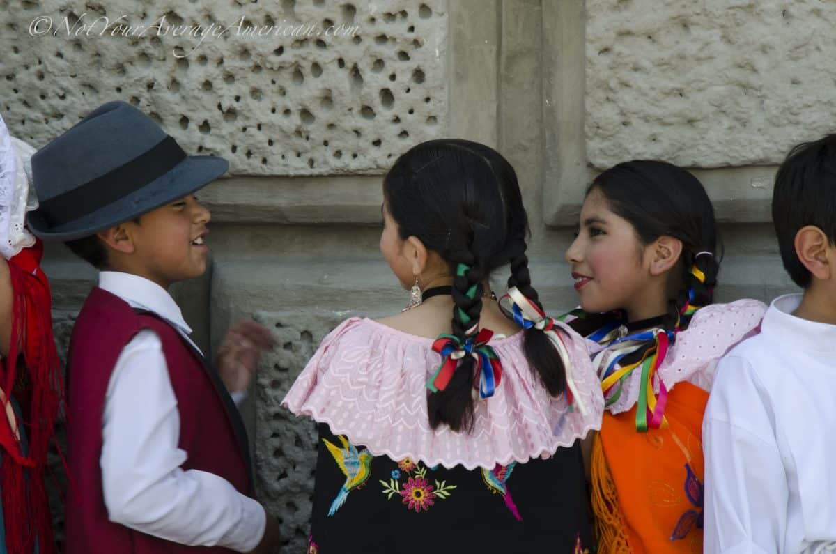 Friends talking before their turn on stage, Palm Sunday, Quito | ©Angela Drake
