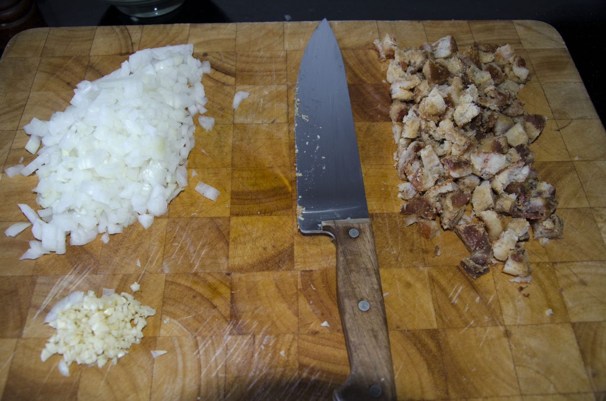 Dice the onions, mince the garlic, and chop the chicharron or other meat into small, bite size pieces.