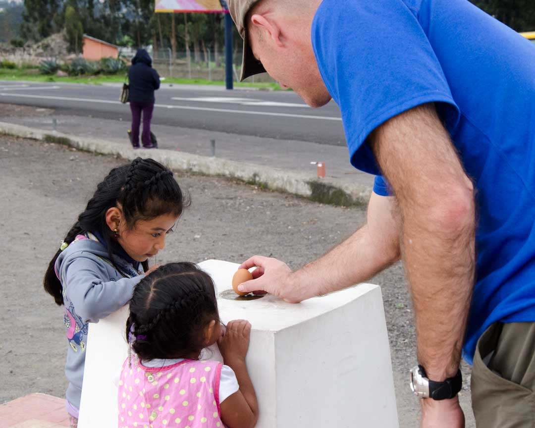 Balancing an Egg at the authentic Mitad del Mundo; Buena Esperanza, Cayambe, Ecuador | ©Angela Drake