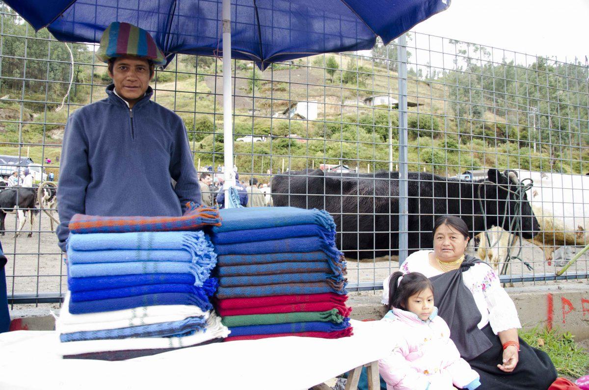 Blanket Vendor and family at the animal market, Otavalo, Ecuador | ©Angela Drake