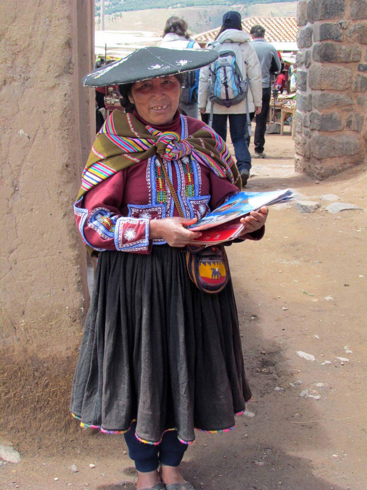 A local woman handing out tourist guides in Raqchi, Peru | ©Angela Drake