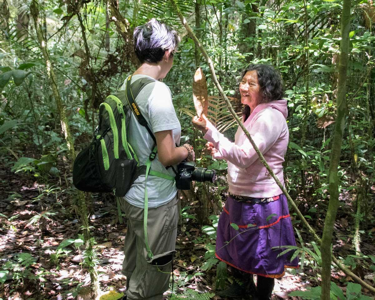 A local Siona guide explaining a medicinal plant to a visitor | Cuyabeno, Ecuador | ©Angela Drake