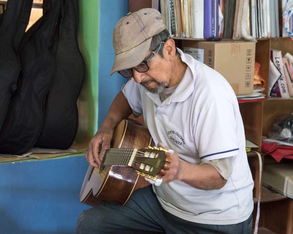 Trying to tune a guitar; San Bartolome, Ecuador | ©Angela Drake